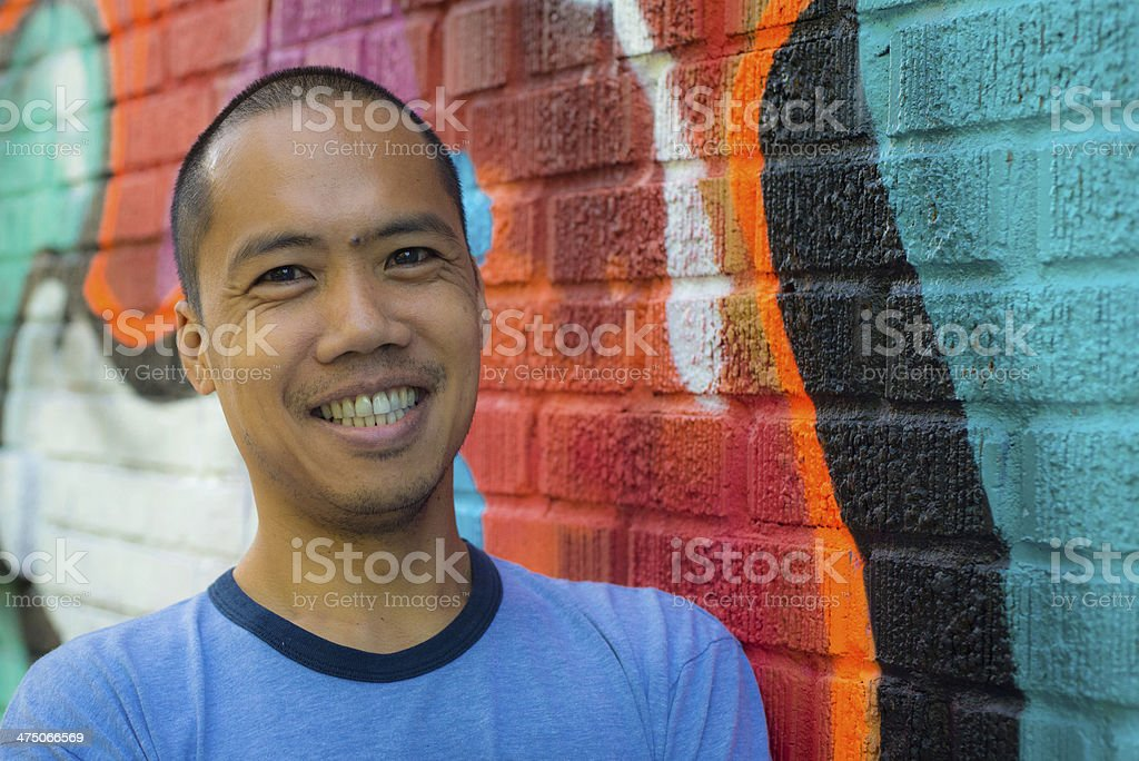 Asian male standing against graffiti wall, smiling stock photo