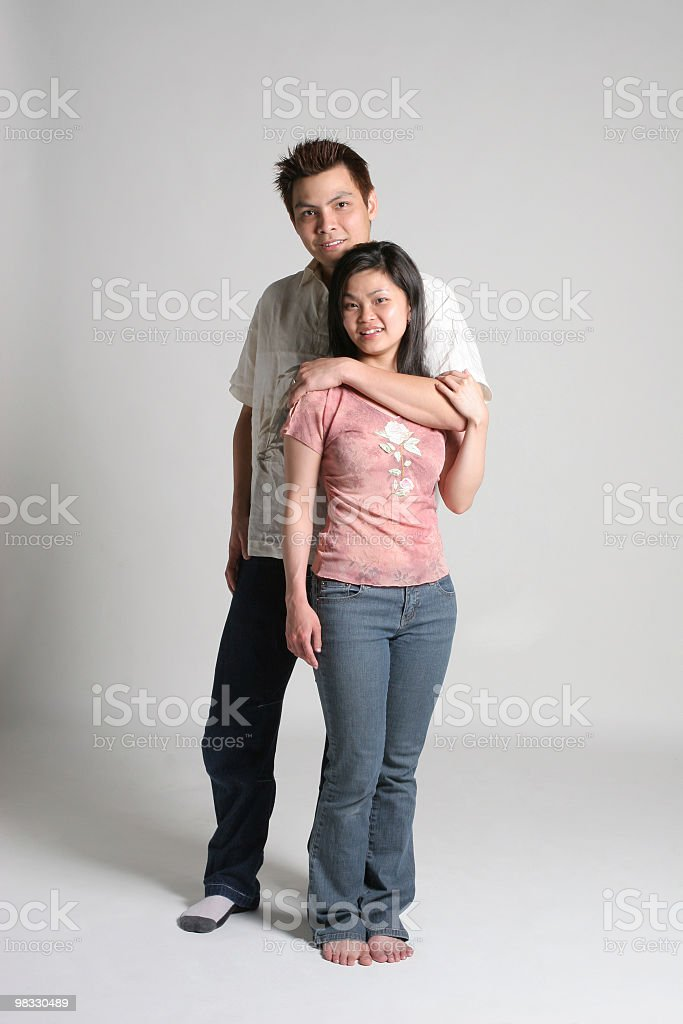 Asian male stands by his female royalty-free stock photo