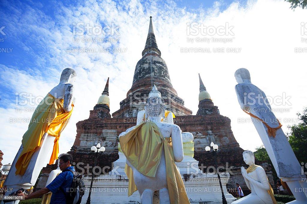 Asian male tourist between group of white thai buddhas stock photo