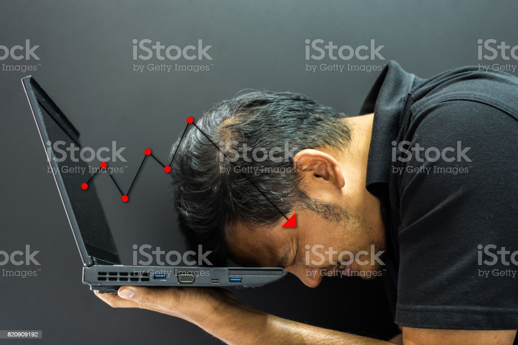 Asian man 40s holding computer laptop with stress in stock market graph business fall down concept stock photo