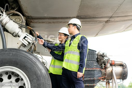 Asian man and woman engineer maintenance airplane team repairs, fixes, modernization and renovation in front airplane from  in airport.