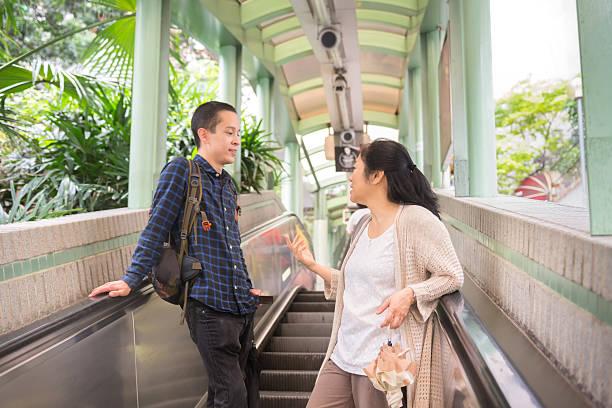 Asian Man and Woman Riding Mid-Levels Escalator, Hong Kong stock photo