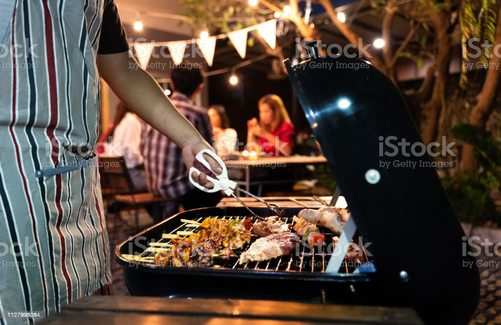 Asian man are cooking for a group of friends to eat barbecue - Стоковые фото Азиатского и индийского происхождения роялти-фри