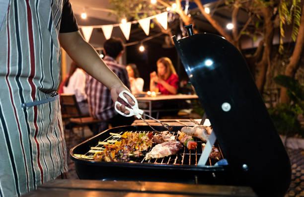 azjatycki człowiek gotuje dla grupy przyjaciół, aby zjeść grilla - grillowany zdjęcia i obrazy z banku zdjęć