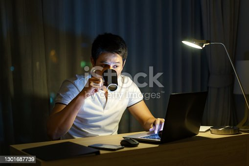 Asian man are drinking tea or coffee while working in late night to relieve drowsiness and make it possible to have a strong to work again.