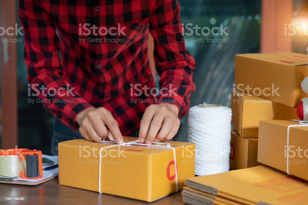 Asian man are packing products to send customers , Packing product...