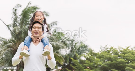 Happy asian father and daughter playing in the park. Asian man carry piggyback little toddler girl. Cheerful family green spring or summer father's day together concept banner