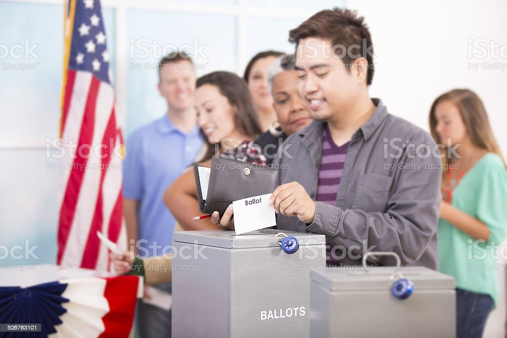 Asian man casts ballot. November USA election. Voters background. stock photo