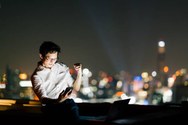 アジアの男性は、スマートフォンやラップトップコンピュータで祝う、成功のポーズ。ビジネス、仕事、または通信ガジェット技術の概念。コピースペース付きの夜の街並みボケの背景 - 特別な日 ストックフォトと画像