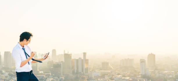 アジアの男性は、屋上、夕日の街のシーンでスマートフォン、成功や応援ポーズで祝います。ビジネス、仕事、または通信ガジェット技術の概念。コピースペースを持つ都市景観の背景 ストックフォト