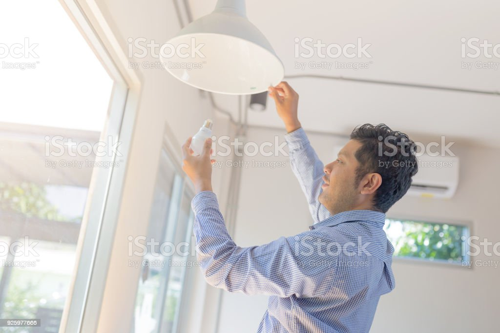 Asian man changing light bulb in coffee shop , installing a fluorescent light bulb stock photo