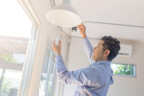 asiatischer mann wechseln glühbirne im coffee-shop, installation einer leuchtstofflampe - glühbirne auswechseln stock-fotos und bilder