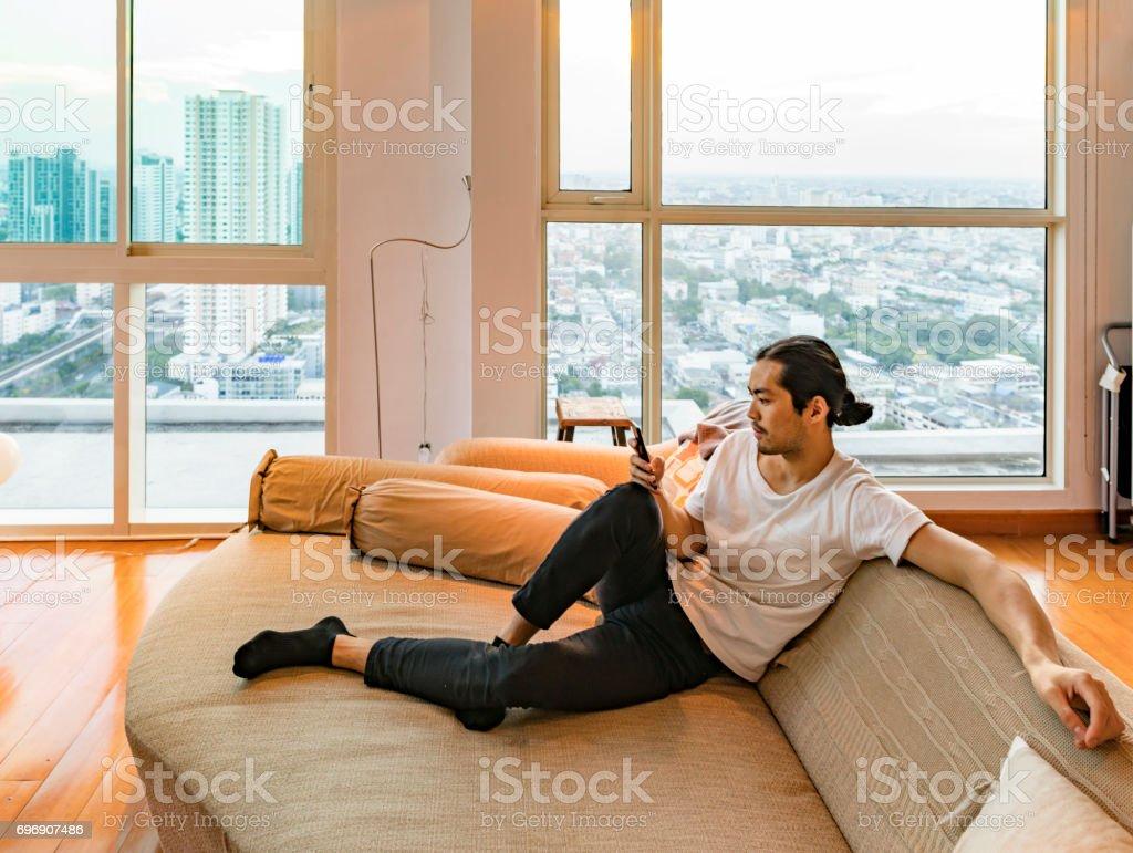 Asiatischer Mann sein Handy in einer Hochhaus-Wohnung überprüfen – Foto