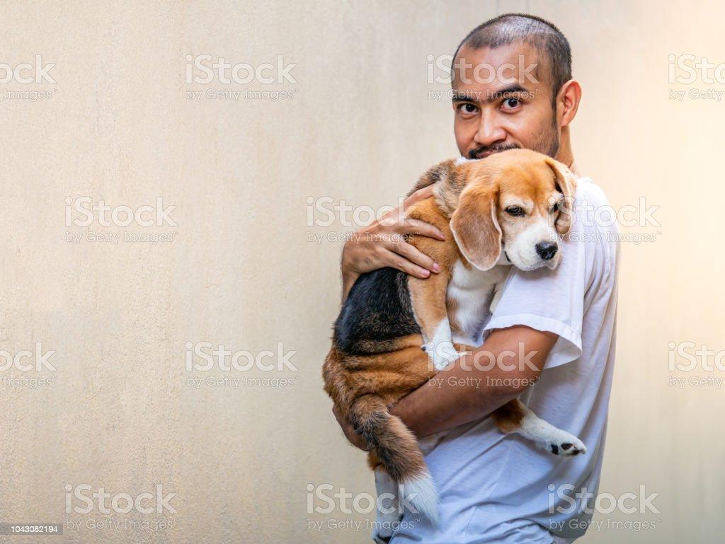 Asiatischer Mann schätzen seine entzückende Beagle Hund tragen. – Foto