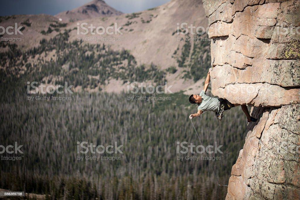 Asian Man Climbing Rock Face stock photo