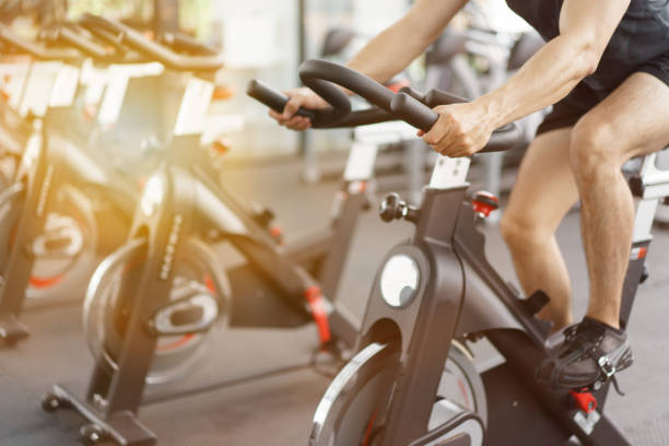 Asian man cycling on bike in fitness gym. Asian man cycling on bike in fitness gym. exercise bike stock pictures, royalty-free photos & images