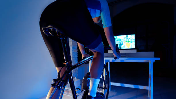 Asian man cycling on the machine trainer he is exercising in the home at night.he play online bike game stock photo