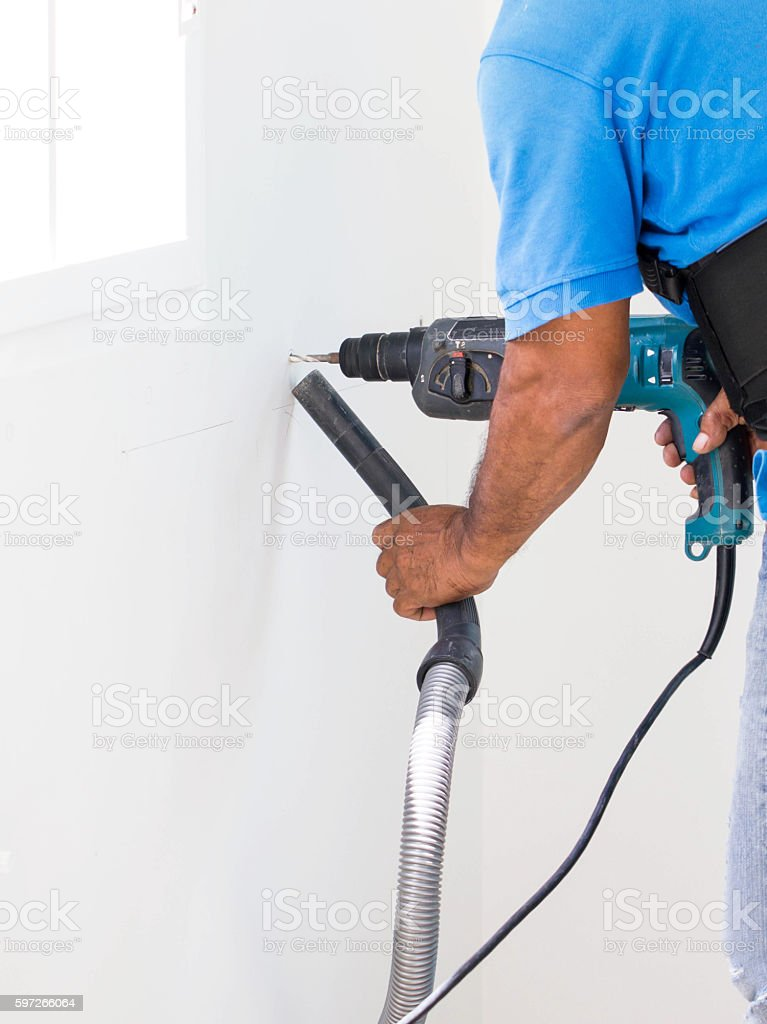 Asian Man Drill On White Wall And Cleaning Dust Lizenzfreies stock-foto