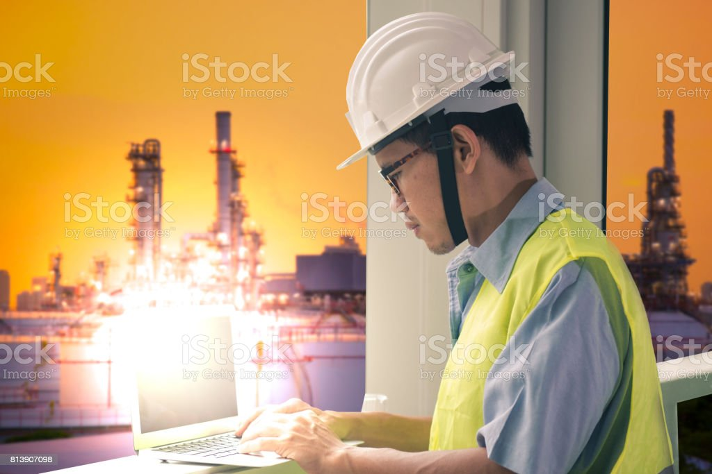 Asian man engineer is using laptop while working inside control room at Oil refinery industry. stock photo