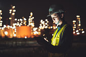 Asian man engineer using digital tablet working late night shift at petroleum oil refinery in industrial estate. Chemical engineering, fuel and power generation, petrochemical factory industry concept