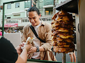 Young asian man fun spending time in Khao San Road. He buying Kebab and enjoying various kinds of street food.