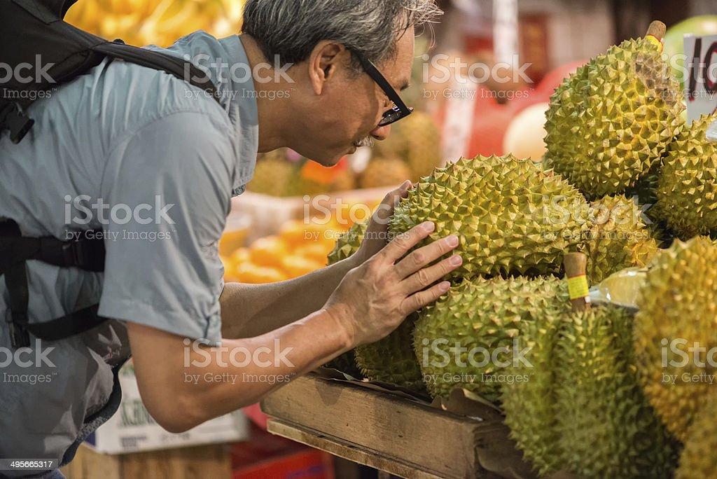 Asian Man Examining Durian Fruit at a Market stock photo