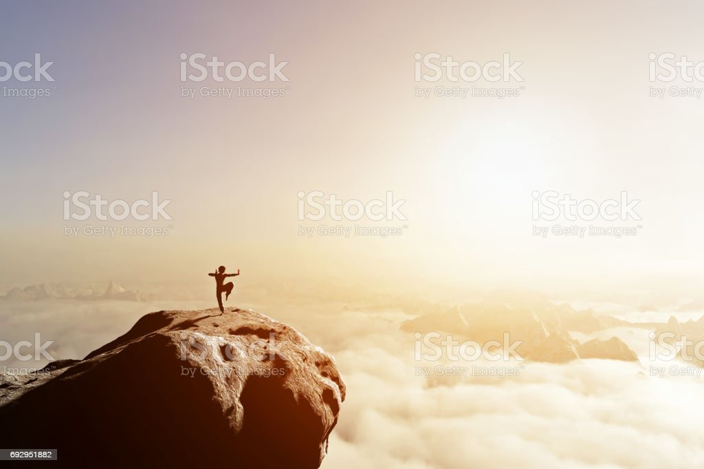 Asian man, fighter practices martial arts in high mountains above clouds. stock photo