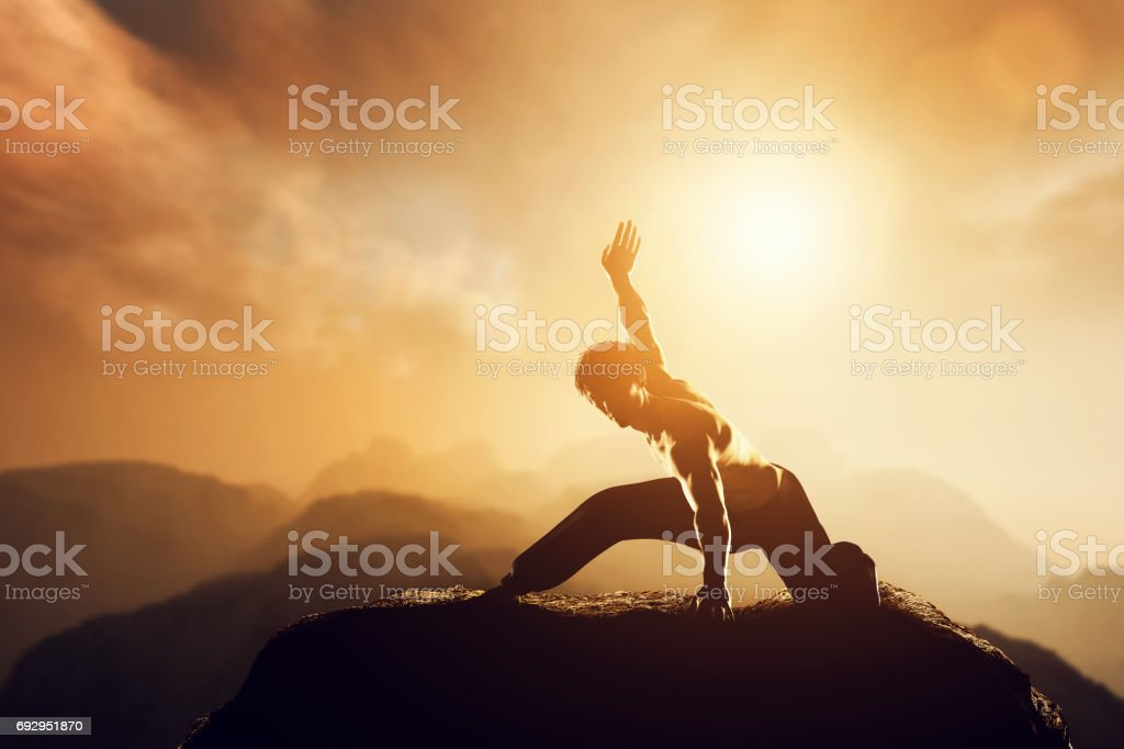 Asian man, fighter practices martial arts in high mountains at sunset. stock photo