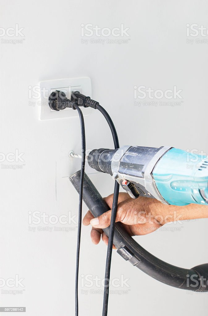 Asian Man Hand Drill On White Wall And Cleaning Dust royalty-free stock photo
