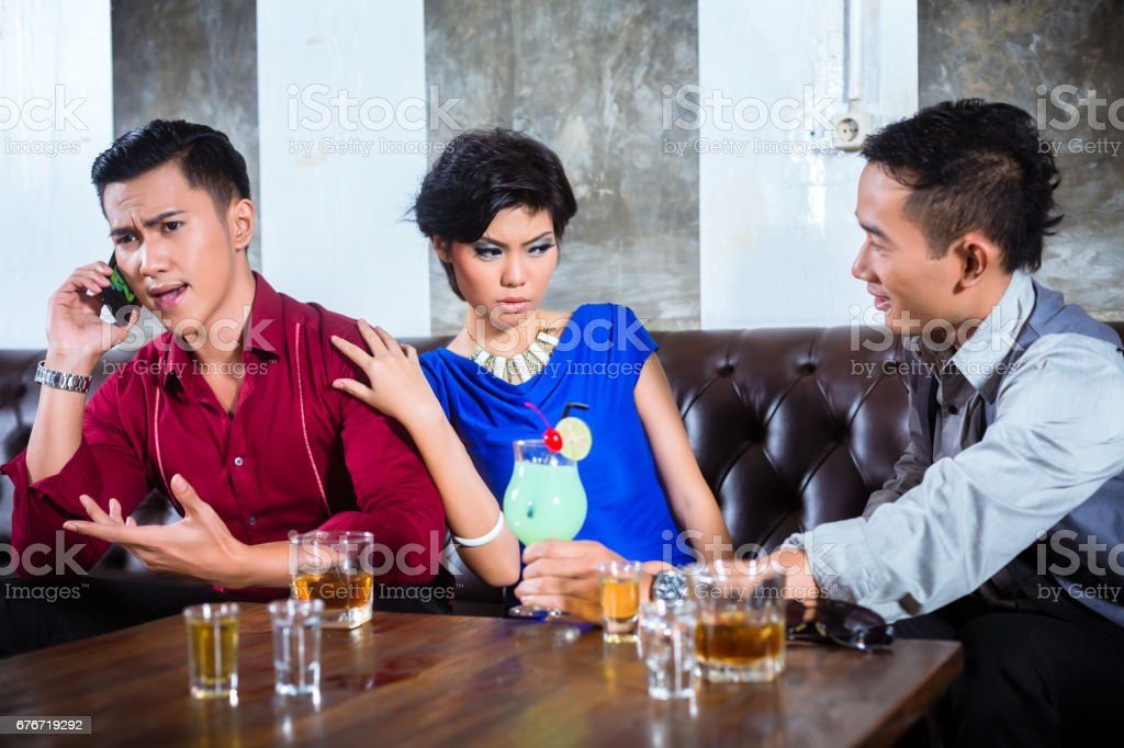 Asian man harassing woman in fancy nightclub stock photo