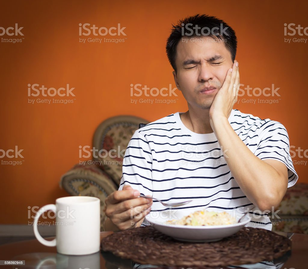 Asian man has a hypersensitive teeth and toothache while eating stock photo