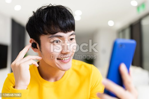 close up of asian young man wearing earbud is having video chat or listening podcast on smartphone with his friend at home