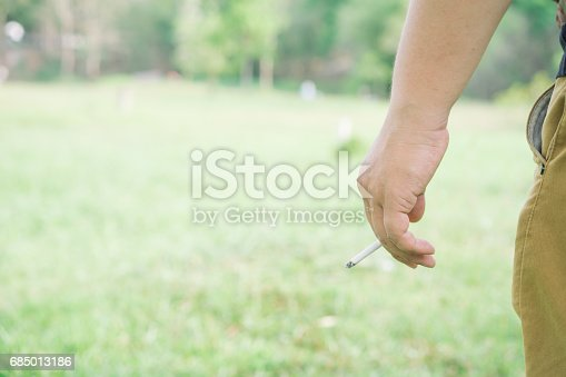 Asian man holding a cigarette on a grass fields  background.