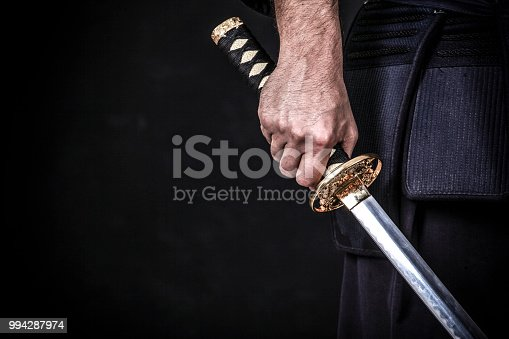 Unrecognizable Asian man holding a katana.