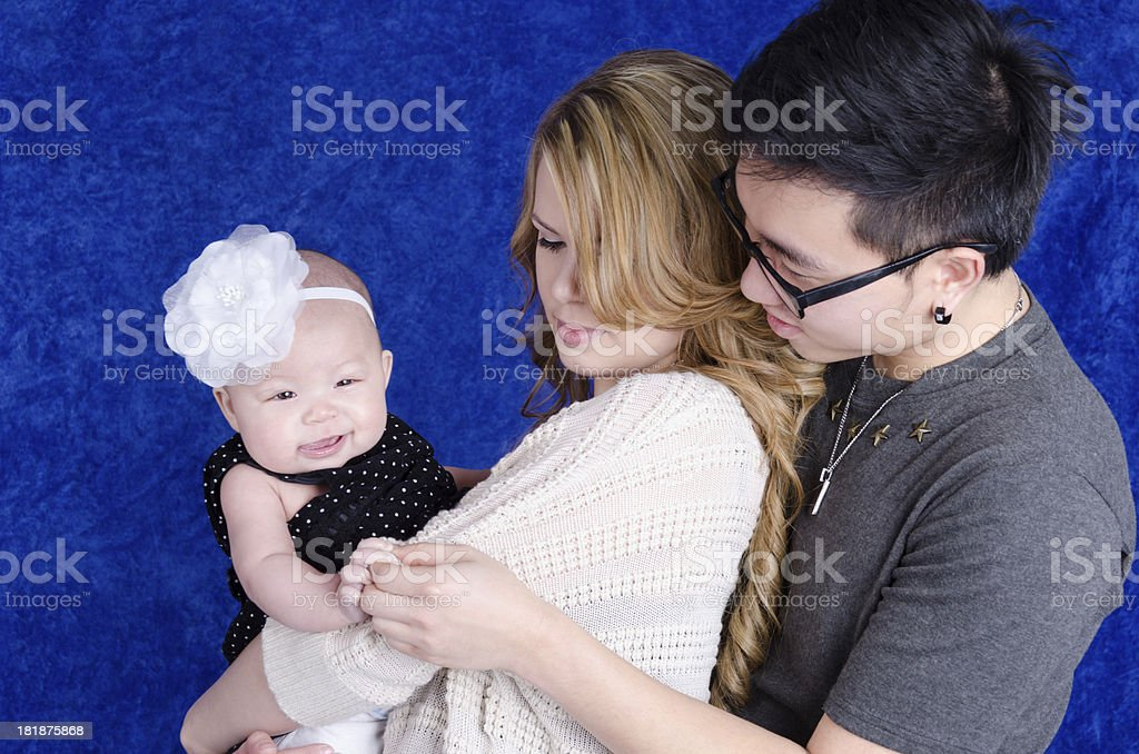 Asian man holding daughter's hand around blonde mother. royalty-free stock photo