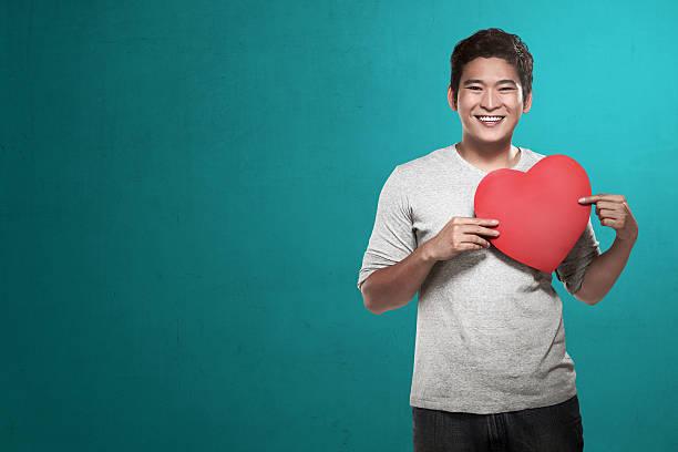 asiático homem segurando coração vermelho - dia do cliente - fotografias e filmes do acervo