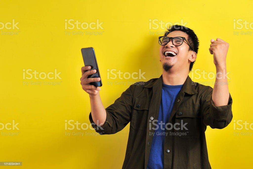 Asian man holding smartphone with winning gesture Asian man holding smartphone with winning gesture. Asian bussinesman winning gift or lottery, on yellow background Adult Stock Photo