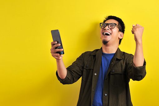 Asian Man Holding Smartphone With Winning Gesture Stock Photo - Download Image Now