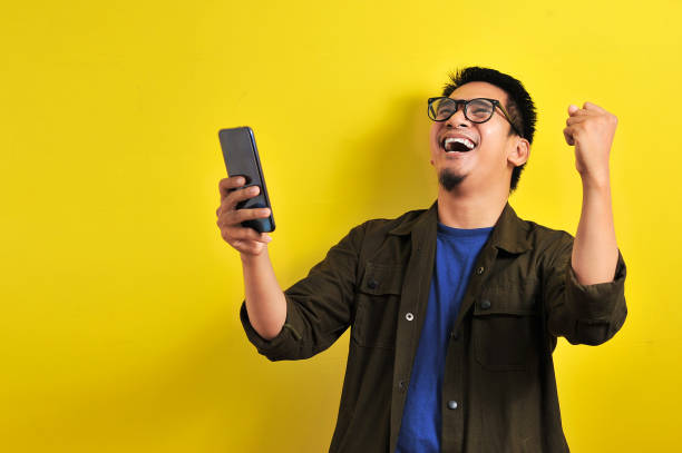 Asian man holding smartphone with winning gesture Asian man holding smartphone with winning gesture. Asian bussinesman winning gift or lottery, on yellow background excited stock pictures, royalty-free photos & images