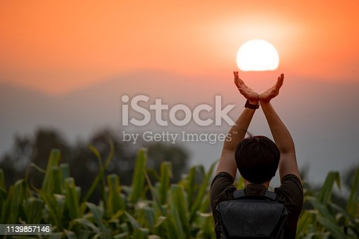 Asian man in corn field raising his arms holding the sun at sunset in summer solstice day. Hope and pray. Achievement concept
