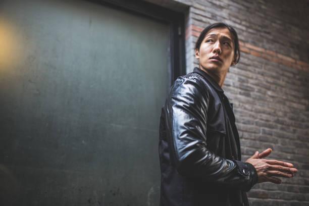 asiatischer mann in lederjacke über schulter - lange jacken stock-fotos und bilder