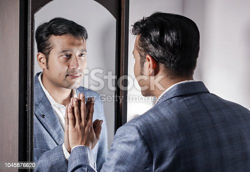 asian man in suit looking after his appearance in front of a mirror beauty styling lifestyle.