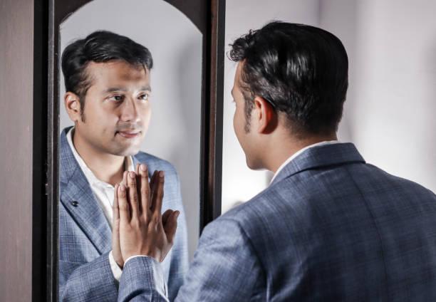 homme asiatique en costume à la recherche après sa comparution devant une miroir beauté style de vie. - miroir photos et images de collection