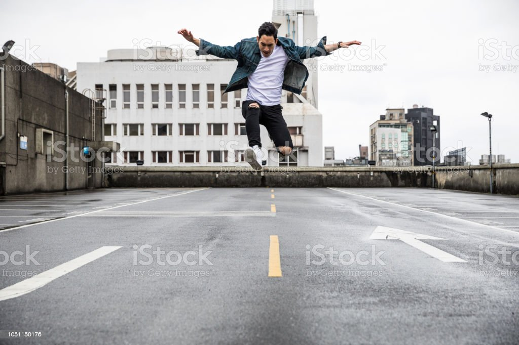 Asian man in urban exploration on the roofs of the city stock photo