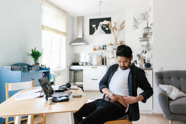 asian man injecting insulin while working from home office - insulina foto e immagini stock
