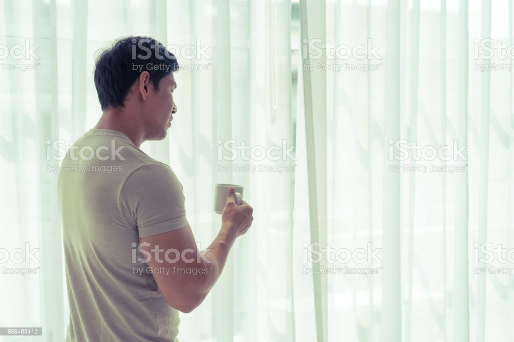 Asian man is drinking tea coffee looking out to morning windows stock photo