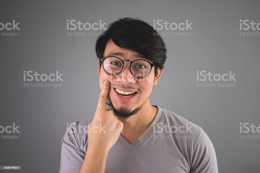 Asian man is faking his smile. stock photo