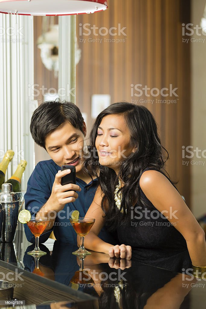Asian man is flirting with woman in bar royalty-free stock photo