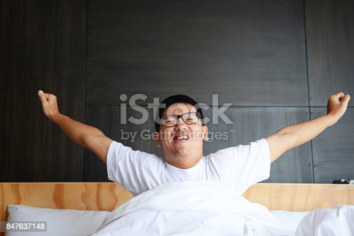istock Asian man is lazy to wake up in the morning at bed room. 847637148