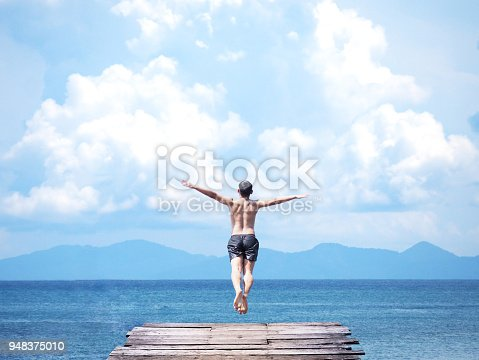 Back view of asian man jumping off wooden bridge into blue sea background. Flying freely to the sky. Summer vacation lifestyle.